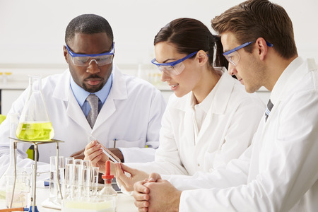 lab technician: Group Of Scientists Performing Experiment In Laboratory Stock Photo
