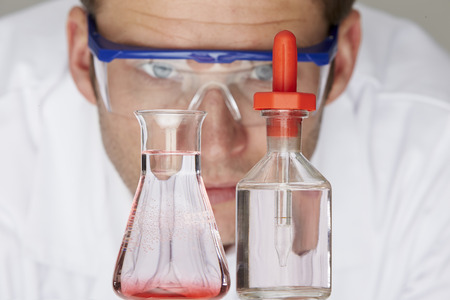 holding close: Scientist Studying Flask And Bottle With Dropper