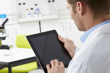 bata de laboratorio: Cient�fico en el laboratorio utilizando la tableta digital Foto de archivo