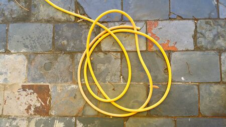water hose: Water Hose Yellow on Slate Floor Stock Photo