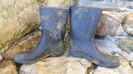 汚れた石の階段にオールド ガーデン ブーツ