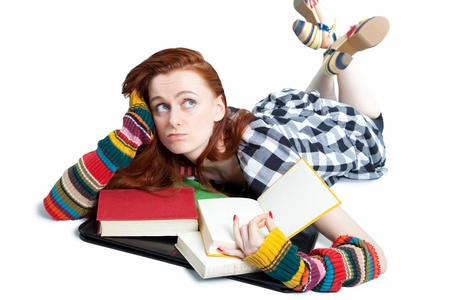 Bored of daydreaming young woman lying on floor with open books; white studio background photo