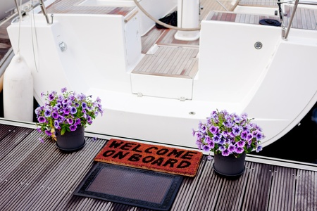 Welcome on board doormat and flowers at the entry to a yacht. photo