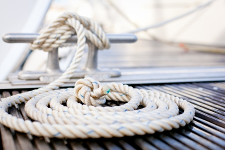 boating: Close-up of mooring rope with a knotted end tied around a cleat on a wooden pier. Stock Photo