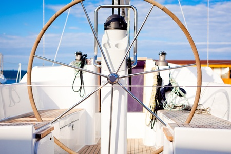 yachting: Steering wheel on a boat with empty seats.