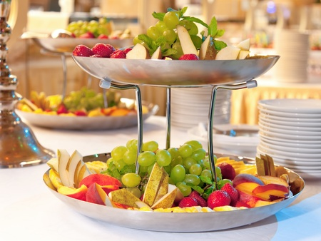 dinning table: Close up on two tiered fruit dishes.