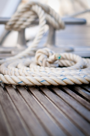 Close-up of a mooring rope with a knotted end on a wooden pier. photo