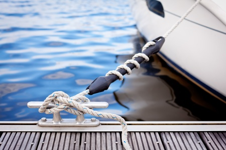 A white yacht moored with a line tied around a metal fixing on the quayside.