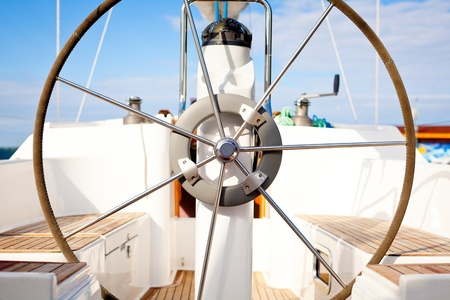 motorboats: A steering wheel on a boat with empty seats.