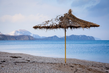 Straw umbrella on beach in winter, Koktebel, Crimea photo