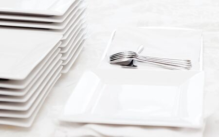 catered: Stack of square white plates and silver spoons at a catered buffet.