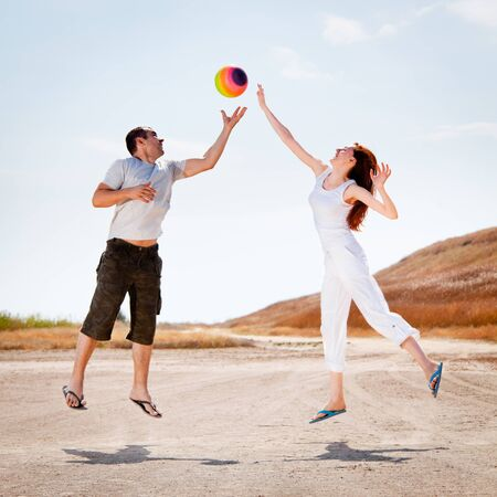 Couple jumping to catch a colorful beach ball, outdoors photo