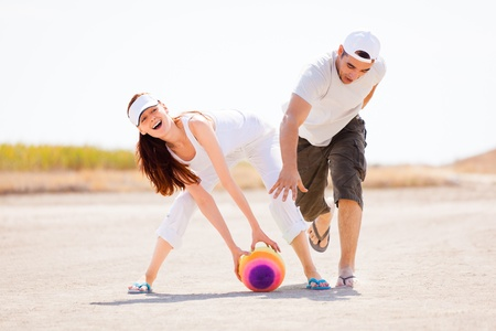 Happy young couple playing with colorful ball outdoors; white sky background and copy space. photo