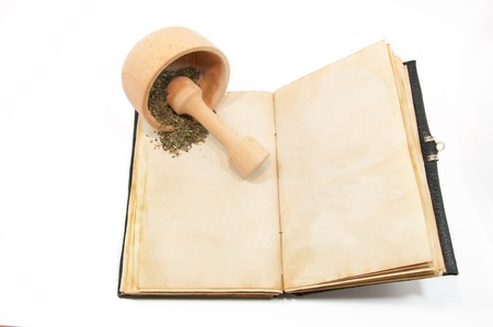 Mortar with herbs on the book photo