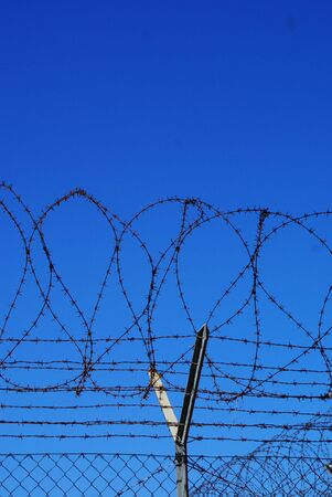 image of barbed wire in front of blue sky