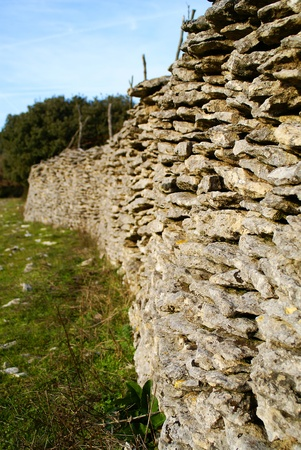 Flat stone wall topped with barbed wire