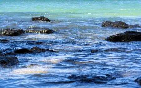 Turquoise ocean waves splashing on rocks Stock Photo - 102012863