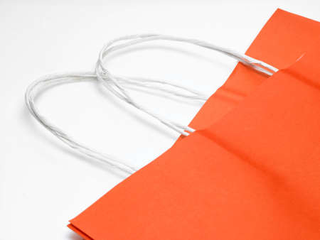 An orange paper bag in white background photo