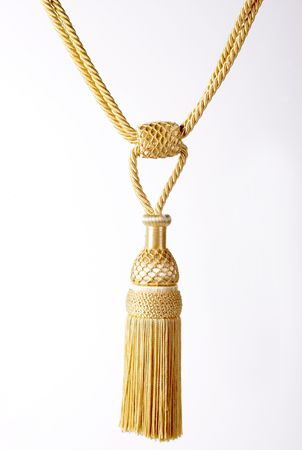 yellow tassel: A yellow colored tassel hanging in white background