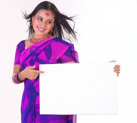 Indian girl in pink sari holding white board photo