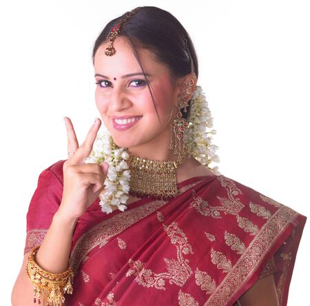 Young girl showing two fingers with red sari photo