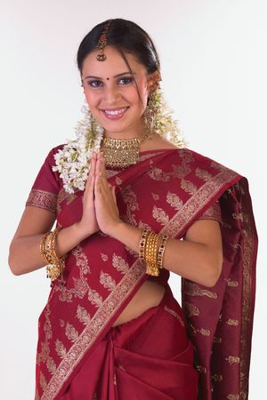 Asian girl with red sari and jewelery in welcome posture