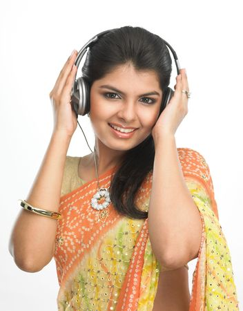 Asian girl in sari listening to music with head phones photo