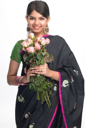 indian meal:  Teenage indian girl in black sari holding bunch of pink roses Stock Photo
