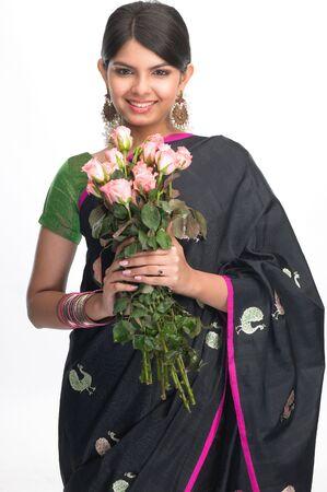 sari:  Teenage indian girl in black sari holding bunch of pink roses Stock Photo