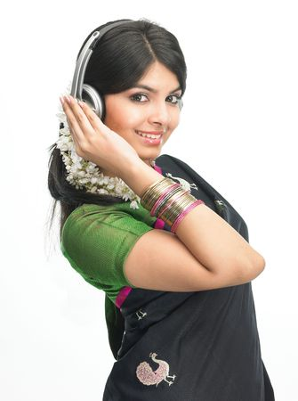 Young girl with beautiful sari and bangles listening to music photo