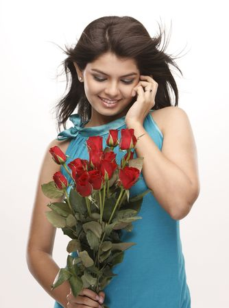 Asian modern girl talking over cellphone with bunch of red roses