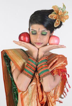 rijke vrouw: Rijke vrouw in een prachtige Bangles en bloem bedrijf twee appels