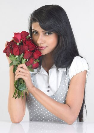 Teenage indian girl with bunch of red roses photo