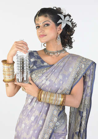 Asian girl in rich fancy sari holding water bottle photo