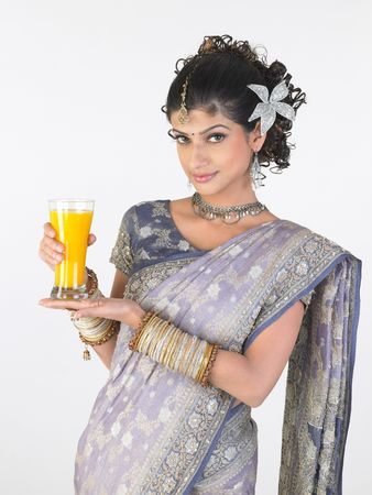 Traditional girl in sari holding mango juice photo