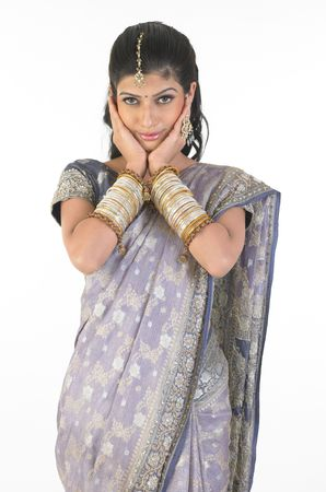 Young girl in fancy sari with her hands on the cheeks photo