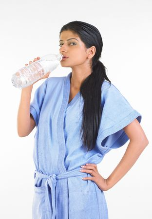 Girl with night-gown drinking water bottle photo