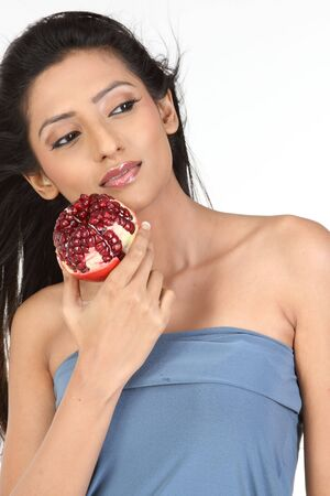 A young attractive girl holding pomegranate photo