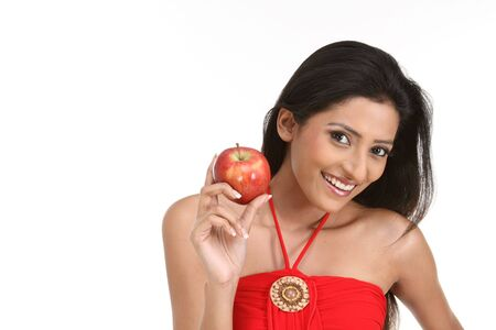 Smiling young girl holding apple reminding you to keep a healthy diet photo