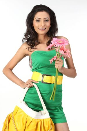 black hair young woman with pink daisy flowers and beautiful yellow hand bag photo