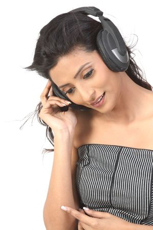 Indian girl enjoying music with the head phones Stock Photo - 6149615