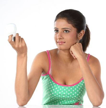 The girl holds burning electric bulb in hands. photo