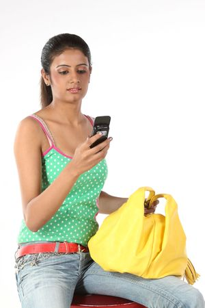 The young woman in elegant clothes looks at a mobile phone photo