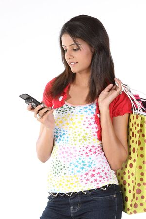 woman with cell holding lots of shopping bags photo