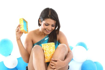 Teenage girl sitting with lots of blue balloons opening her present box photo