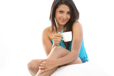indian style sitting: Young girl with pillow having cup of coffee Stock Photo