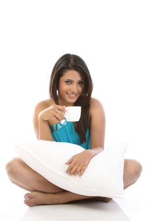 sexy girl sitting: Young girl with pillow having cup of coffee Stock Photo