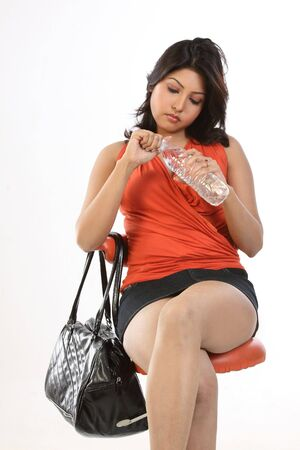Indian teenage girl sitting on chair black leather bag and water bottle photo