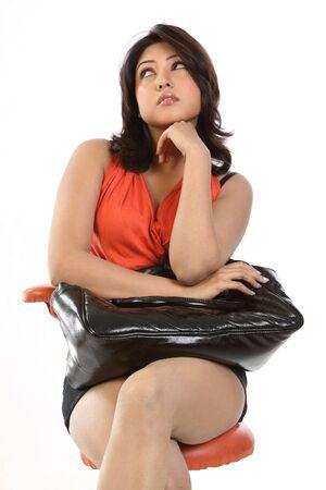 teenage girl sitting with big black bag in thinking gesture photo