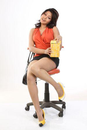 teenage girl sitting on chair black leather bag and gift box photo